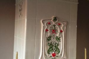Malowany kaflowy element centralny podkreśla klasyczny styl pieca