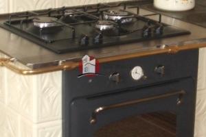 Kafle piecowe w kolorach krem/brąz nawiązują do rustykalnego charakteru płyty gazowej i piekarnika