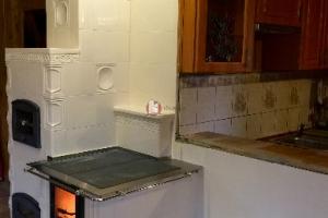 Prawą stronę kuchni kaflowej wypełnia ławka ze schowkiem na drewno