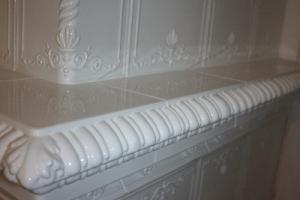 Ozdobna półka stanowi również przewężenie pieca kaflowego, nadając mu lekkości.