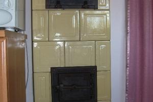 Ścianka pieca kaflowego z żeliwnym piekarnikiem i drzwiczkami.